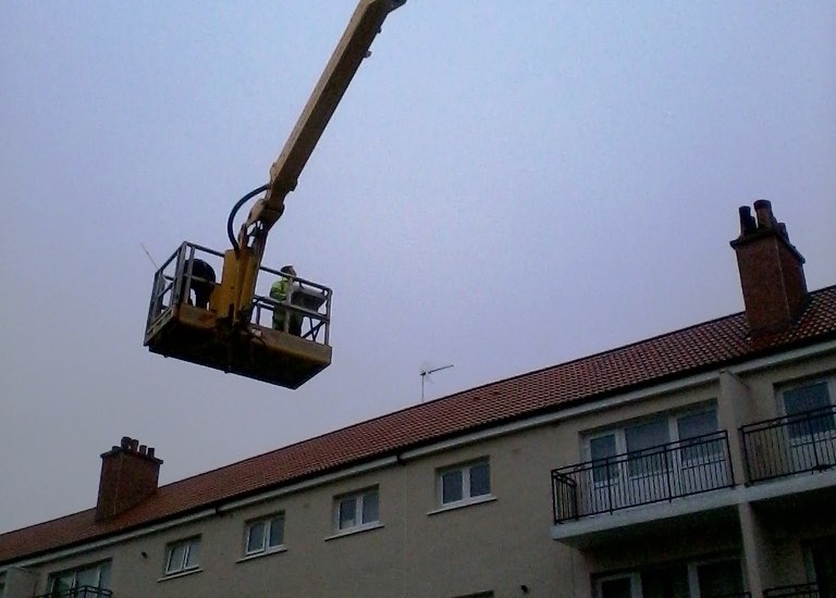 Roofers moving Skylift MEWP into position