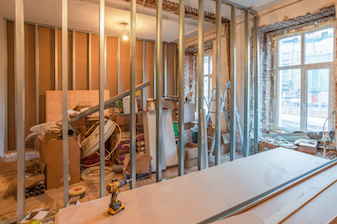 Builders contructing wall with plasterboard