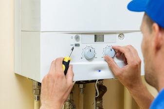 Heating engineer installing boiler in home